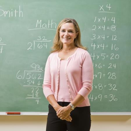 writing western: Teacher standing near blackboard