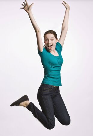 rooting: Teenage girl jumping in mid-air Stock Photo