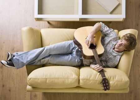 Man laying on sofa playing guitar photo