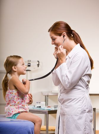 stethoscope: Doctor giving girl checkup in doctor office