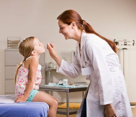 Doctor checking girl temperature Foto de archivo