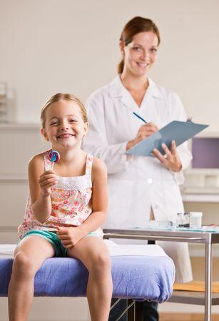 Girl eating lollipop in doctor office photo