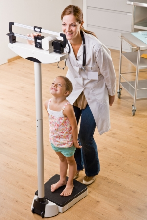 Doctor weighing girl in doctor office