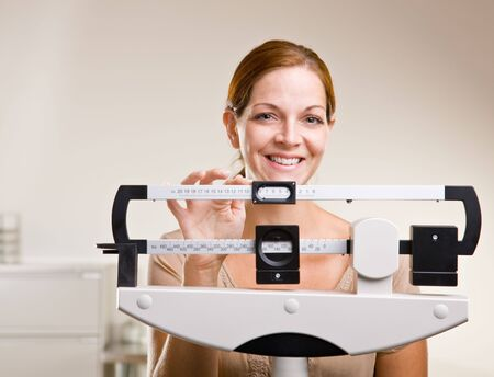 weighing scale: Woman weighing herself in doctor office