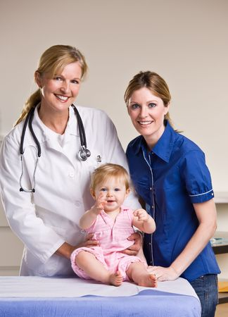 Doctor, mother and baby girl in doctor office photo