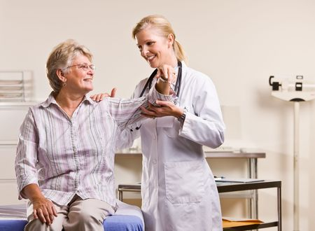 attired: Doctor checking senior woman arm