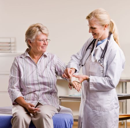 attired: Doctor adjusting senior woman wrist splint Stock Photo