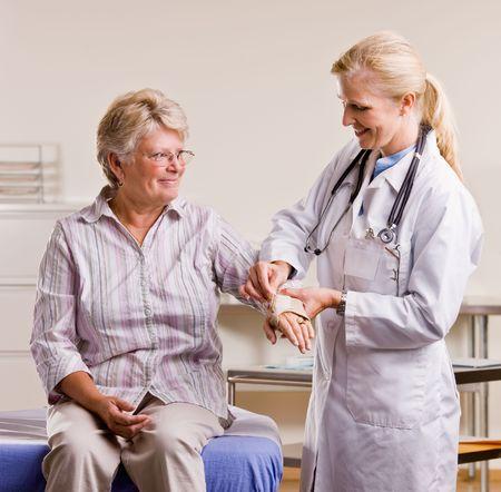 Doctor adjusting senior woman wrist splint Foto de archivo