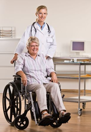 attired: Senior woman sitting in wheelchair with doctor Stock Photo