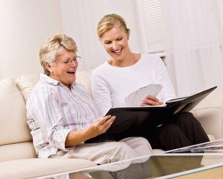 Senior woman and daughter looking at photographs photo