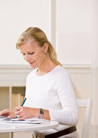 meticulous: Woman writing checks Stock Photo