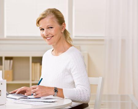 Woman writing checks Stock Photo