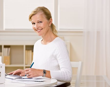 paying: Woman writing checks Stock Photo