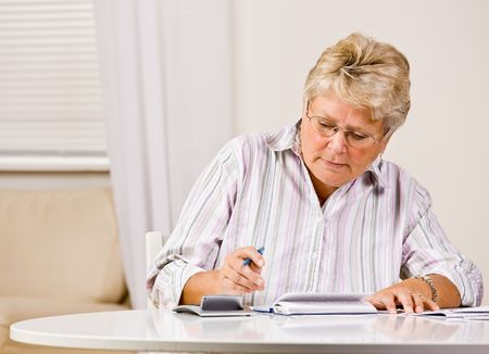 meticulous: Senior woman writing checks