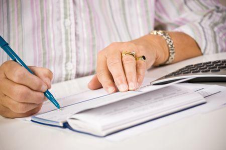 pagando: Mujer Senior escribir cheques Foto de archivo