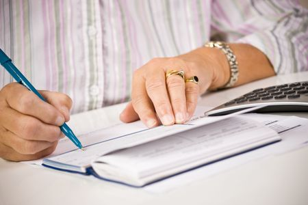 Senior woman writing checks photo