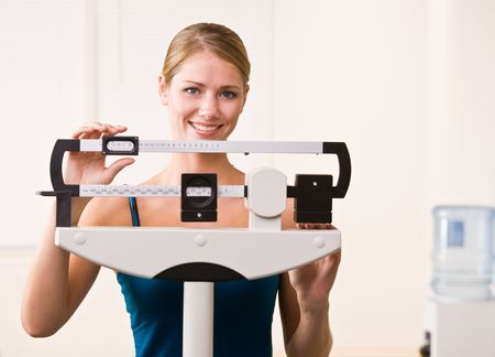 Woman weighing herself on scales in health club Banque d'images