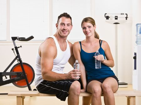 Man and woman drinking water in health club photo