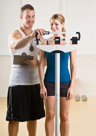 フィットネス センターでパーソナル トレーニング体重の女性