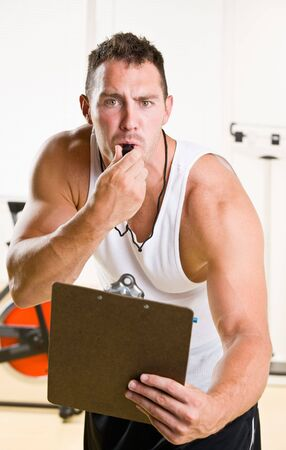 Personal trainer blowing whistle in health club photo