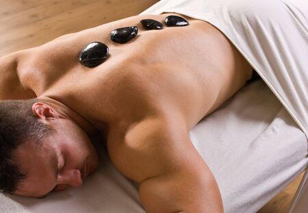 adult massage: Man receiving hot stone therapy massage