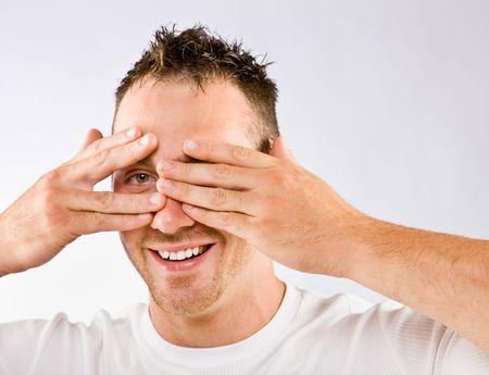 peering: Man peering from behind hands