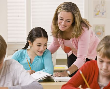 writing western: Teacher helping student in classroom