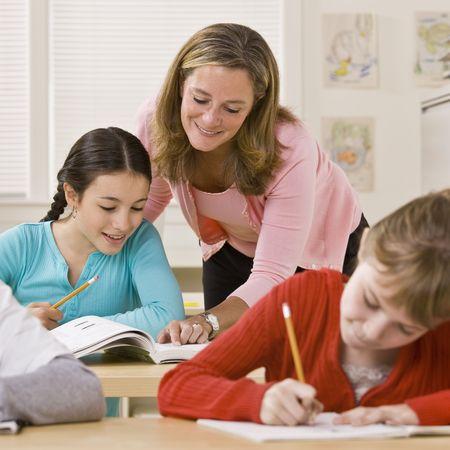 docenten: Leraar te helpen student in klas Stockfoto