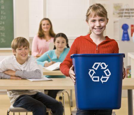 Student carrying recycling bin Foto de archivo