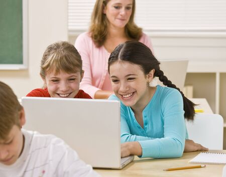 Girls using laptop in classroom