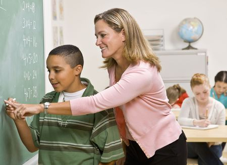 Teacher helping student at blackboard Foto de archivo