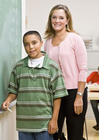 Teacher helping student at blackboard Stock Photo - 6583143