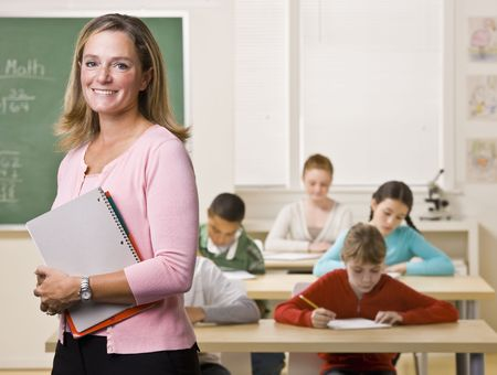teacher with students: Teacher standing with notebook in classroom