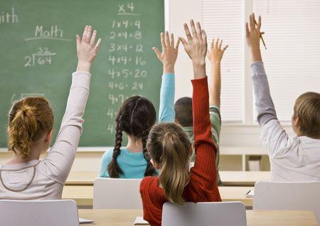 ni�os en la escuela: Estudiantes respondiendo a la pregunta del profesor Foto de archivo