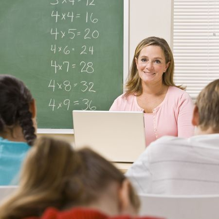 use computer: Teacher with laptop in classroom