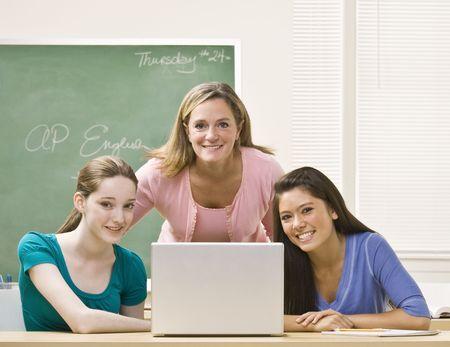 Teacher helping students on laptop