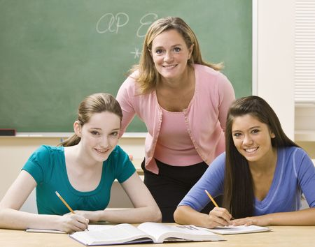 writing western: Teacher helping students study Stock Photo