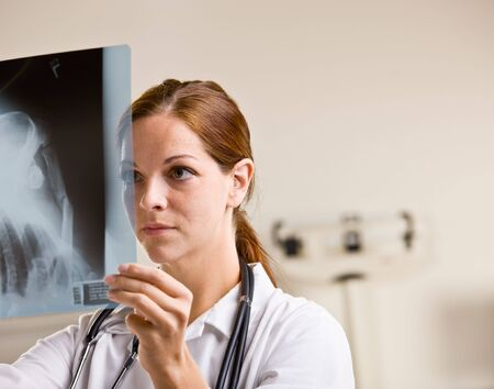 attired: Doctor reviewing x-rays in doctor office Stock Photo