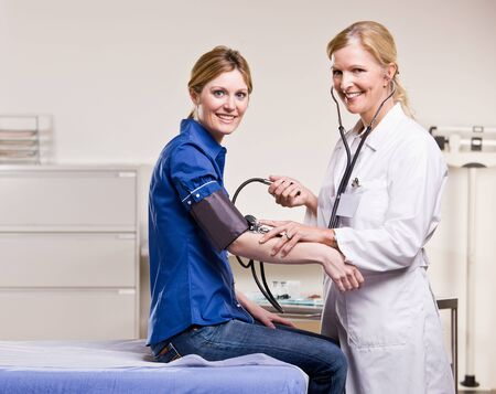 Doctor checking woman blood pressure