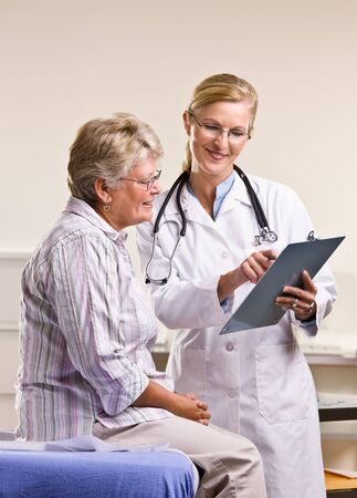 attired: Doctor explaining medical chart to senior woman Stock Photo