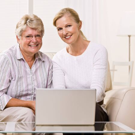 Senior woman and daughter using laptop photo