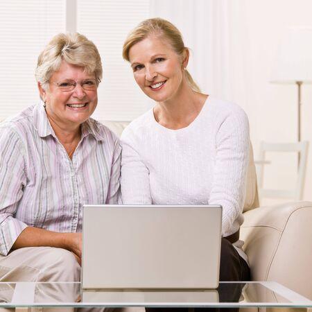 Senior woman and daughter using laptop photo
