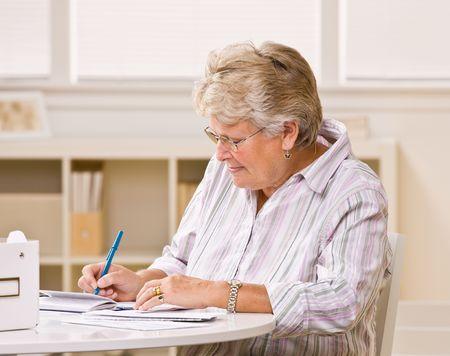 writing western: Senior woman writing checks