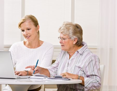 typist: Senior woman writing checks with daughter help Stock Photo