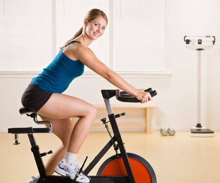 Woman riding stationary bicycle in health club photo