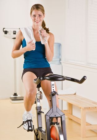 Woman riding stationary bicycle in health club Stock Photo - 6582358
