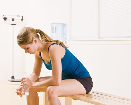 Woman drinking water in health club photo