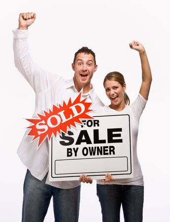 Couple cheering and holding for sale sign photo
