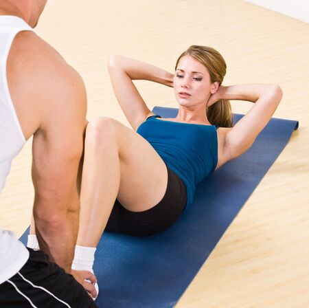 Trainer helping woman do sit ups Stock Photo