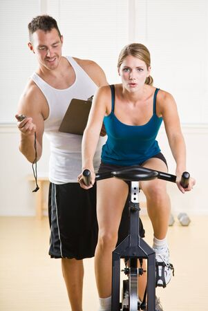 timing: Trainer timing woman on stationary bicycle